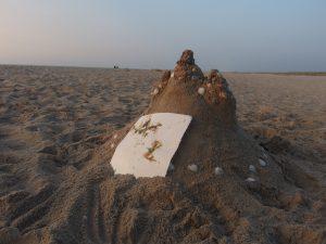 zandkasteel met papier met zeewier